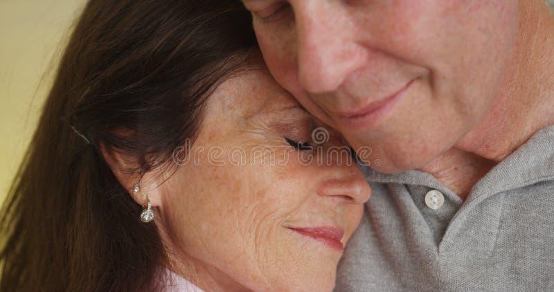 Loving older couple hugging each other stock images