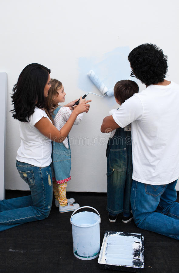 Loving Parents Helping Their Children To Paint Stock Photo
