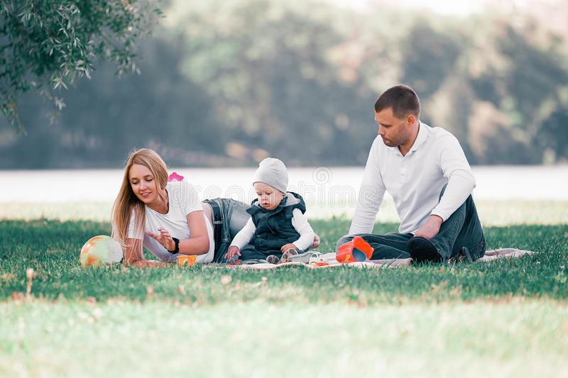 Loving parents and their little son sitting on the lawn on a summer day. royalty free stock photos