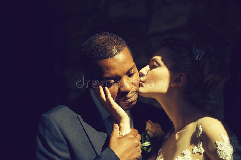 Loving pretty girl or beautiful bride kissing handsome man royalty free stock image