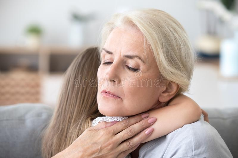 Loving sad grandmother embracing little girl comforting supporti stock images