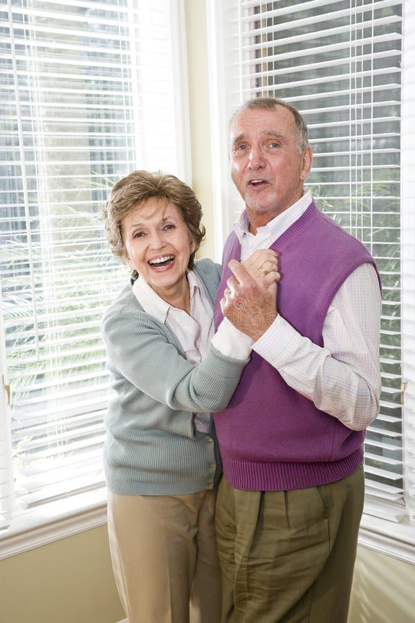 Loving senior couple dancing in living room. Happy senior couple dancing together in living room royalty free stock image