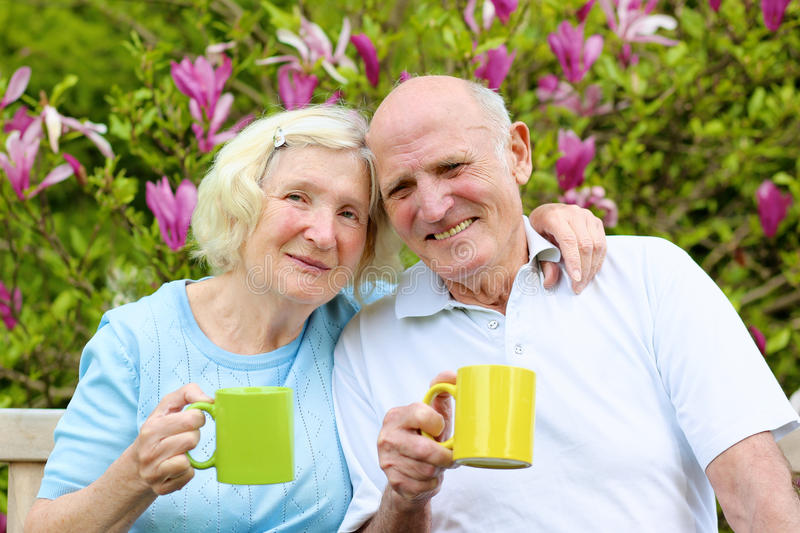 Loving senior couple drinking tea in the garden. Happy loving senior couple drinking tea from big colorful mugs. They are sitting on a wooden bench in the garden stock photo