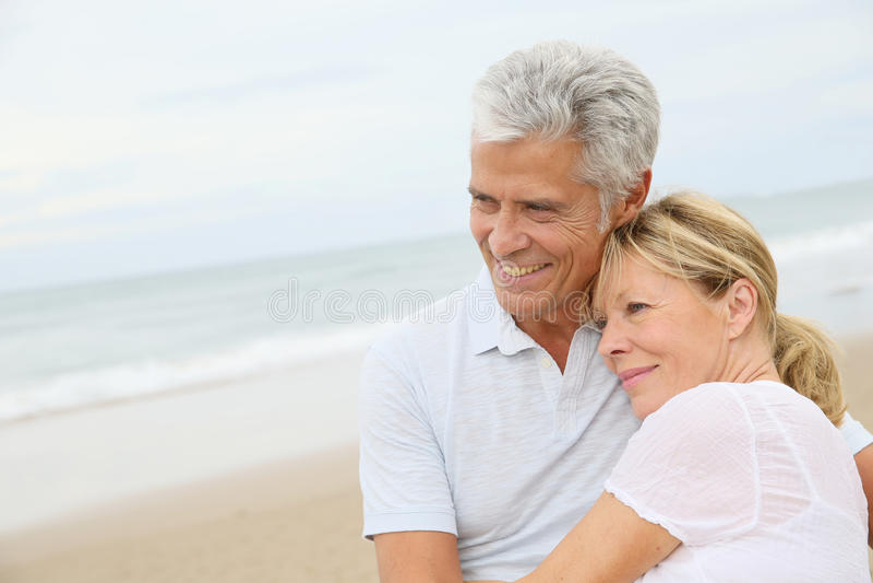 Loving senior couple embracing on the beach royalty free stock image