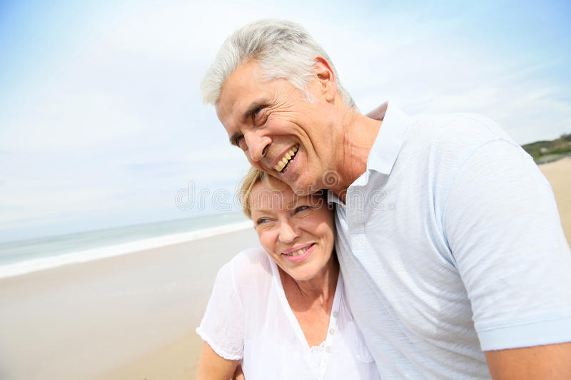 Loving senior couple embracing on the beach royalty free stock photos