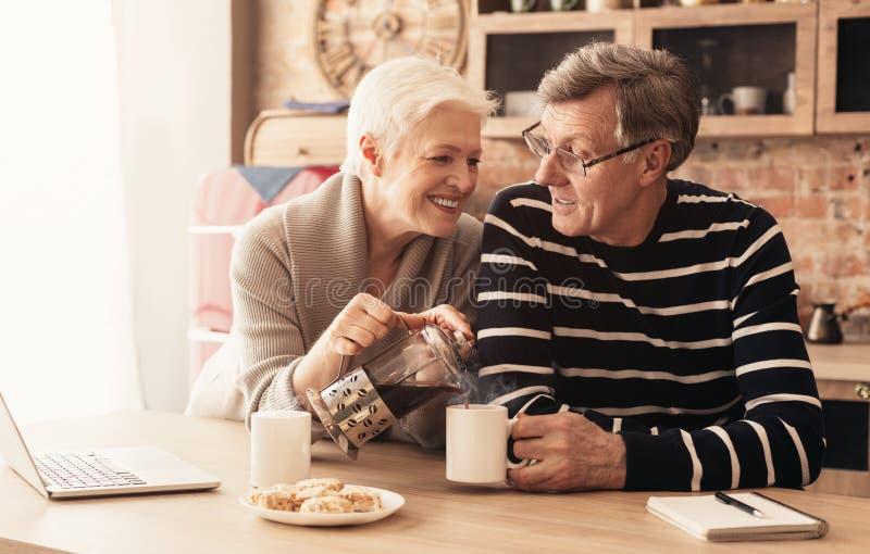 Loving senior couple enjoying morning together at kitchen royalty free stock image