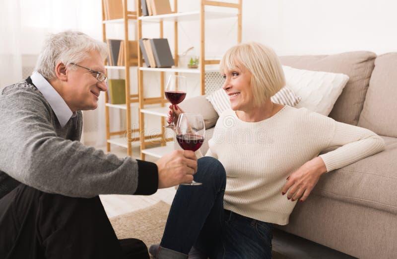 Loving senior couple enjoying wine at home. Loving senior couple enjoying wine, having rest at home royalty free stock photo