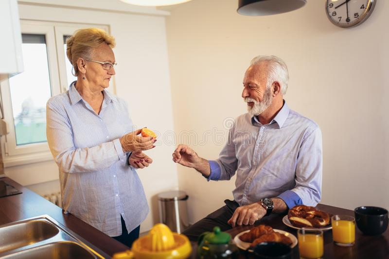 Loving senior couple having fun preparing healthy food on breakfast in the kitchen stock images