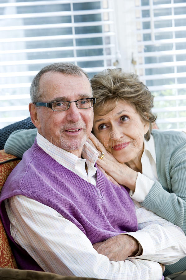 Loving Senior Couple Sitting Together On Couch Stock Images