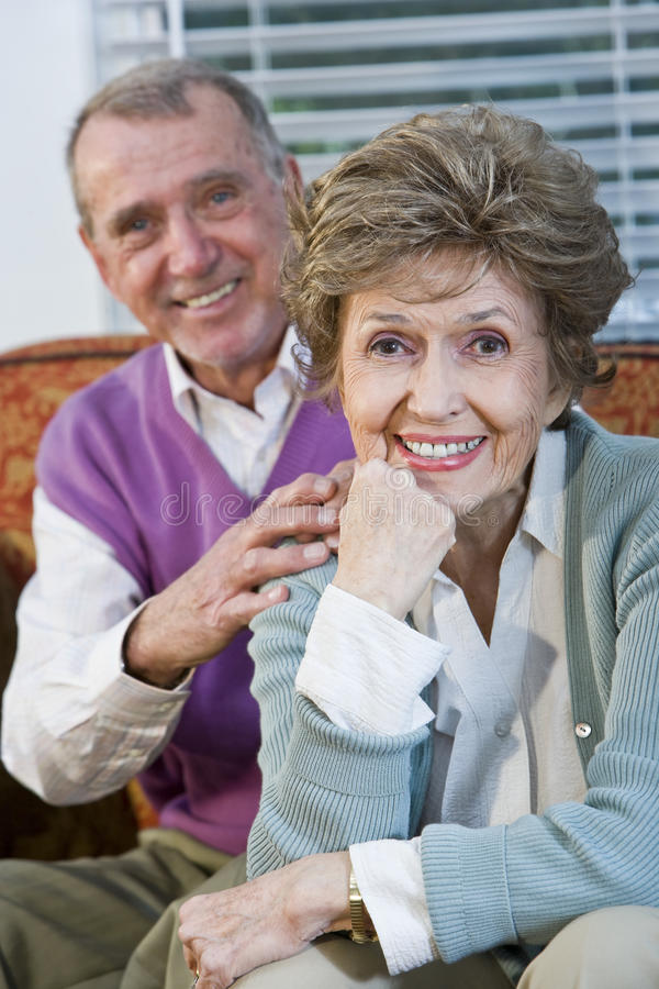 Loving senior couple sitting together on couch. Portrait of happy affectionate senior couple on couch stock photo