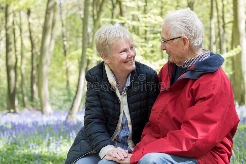 Loving Senior Couple Taking Break On Walk Through Bluebell Wood stock photos