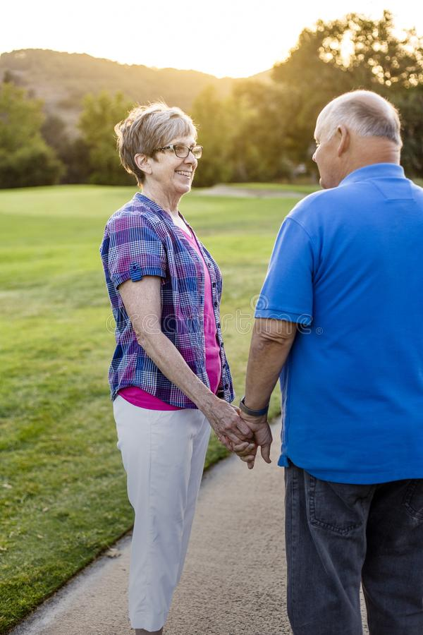 A loving senior couple on a walk together at sunset royalty free stock images