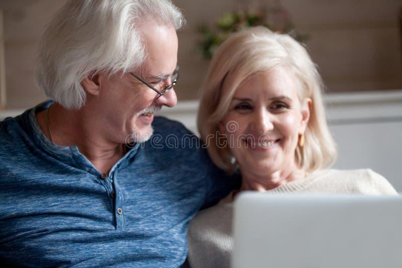 Loving senior husband looking at smiling mature wife using lapto royalty free stock images