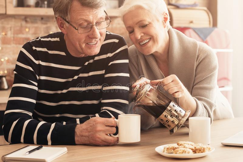 Loving senior woman pouring fresh tea to her husband`s cup stock photography