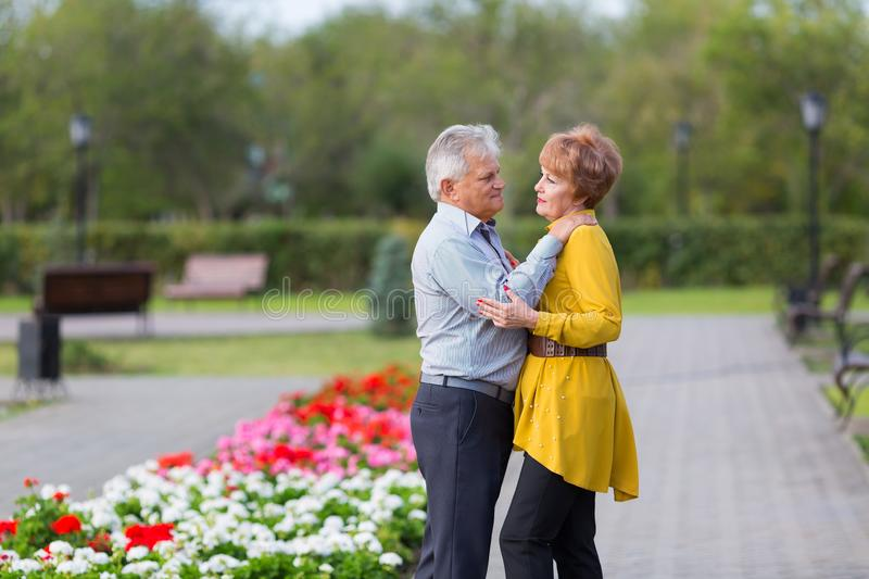 Loving seniors in the park. Man and woman pensioners gently hug each other a city park royalty free stock photo