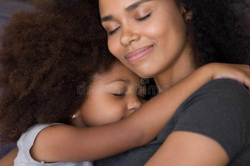 Loving single black mother hugs cute daughter feel tenderness connection. Happy african mum caressing embracing little girl, mommy kid cuddle, warm royalty free stock image