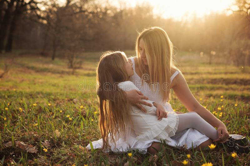Happy family walks in the spring meadow. Loving single mother holds an upset daughter in tender embraces. Caring mother supports girl in a difficult moment stock photos