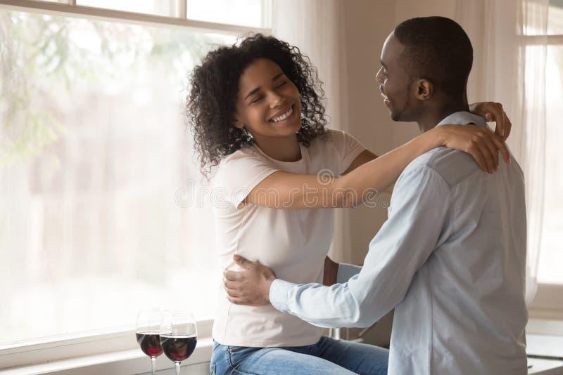 Happy biracial couple hug enjoying romantic date at home. Loving smiling african American millennial couple hug relax at home kitchen drinking wine celebrating stock photos