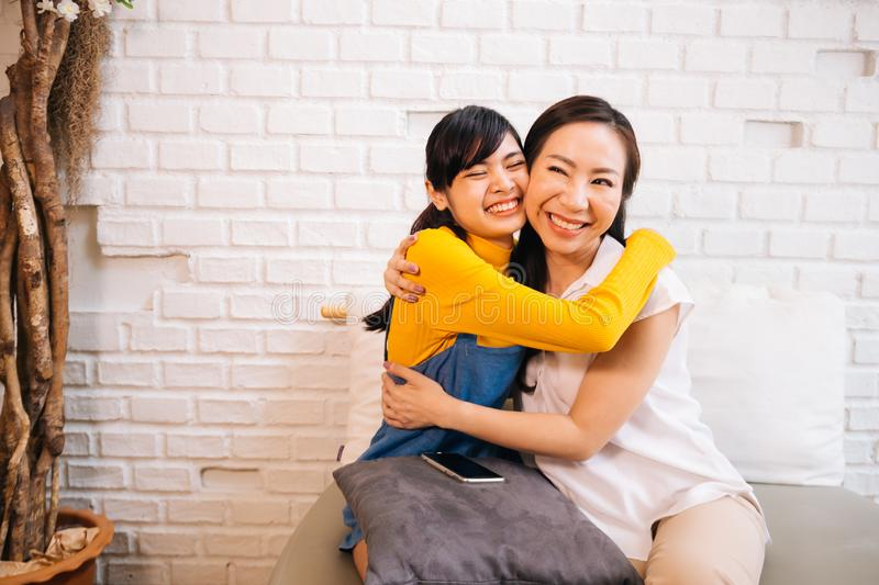Cheerful Asian mother and daughter embracing while sitting on sofa royalty free stock photography