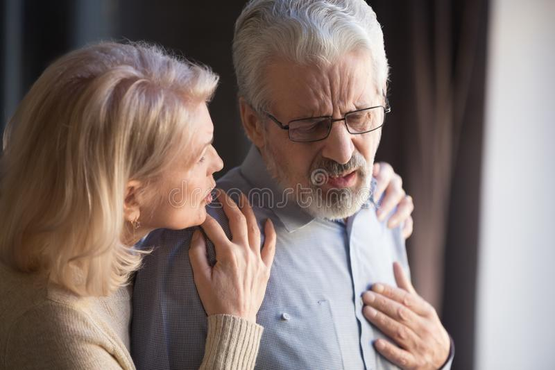 Senior wife help spouse touching chest having heart attack royalty free stock photography
