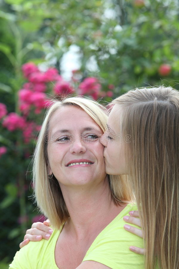 Loving teenager kissing her mother royalty free stock photo