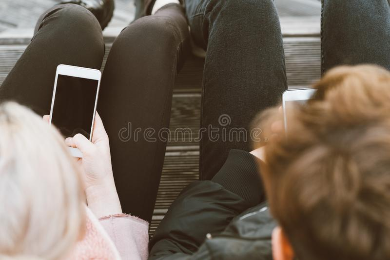 Loving teenagers on date look at mobile phones, sit on park bench in fall. Immersion in virtual world, social networks. Concept of. Loving teenagers on date look stock photography