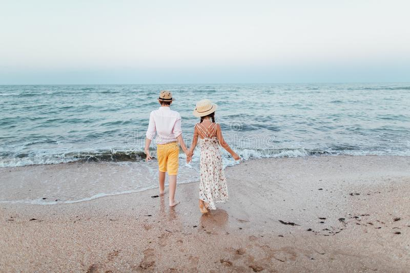 A boy and a girl stand on the beach with their backs and hold hands. Romantic story on the seafront. Loving teenagers. Romantic story on the seafront. A boy and royalty free stock photo
