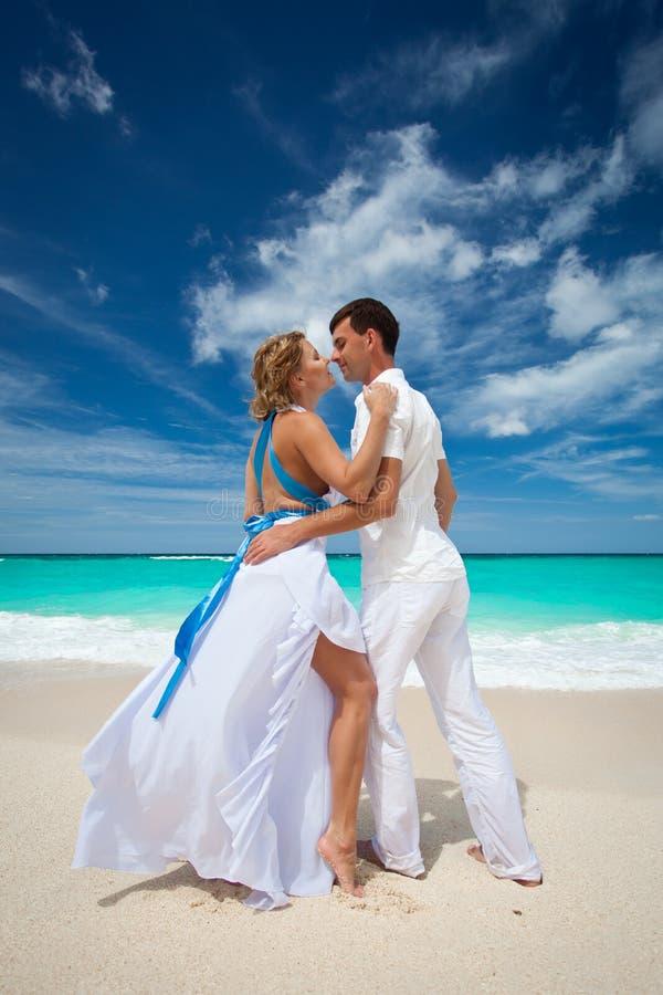 Loving wedding couple on beach stock images