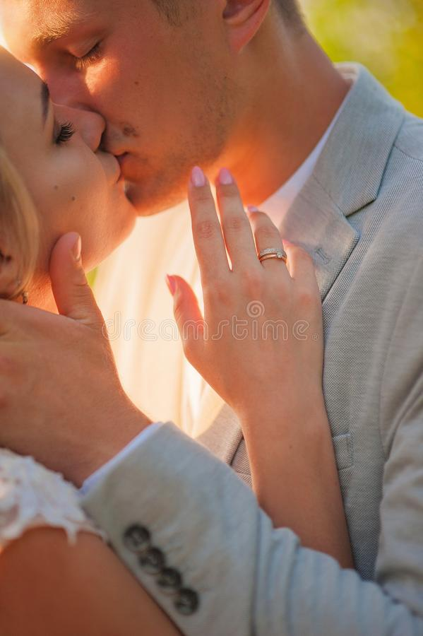 Loving wedding couple hugs and kisses in the summer at sunset. The concept of romantic relationship, idyll. Close-up kiss and tend. Er hugs royalty free stock photo