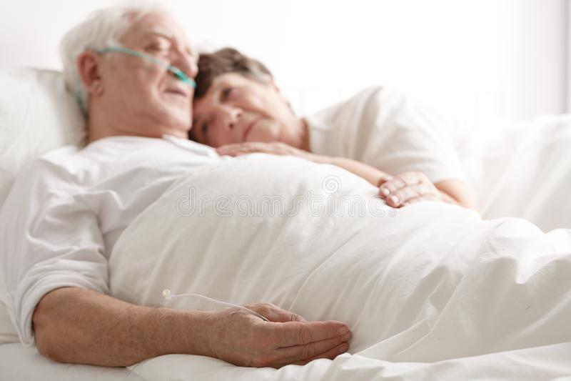 Loving wife hugging sick husband. Loving wife hugging seriously sick elderly husband in hospital royalty free stock photography
