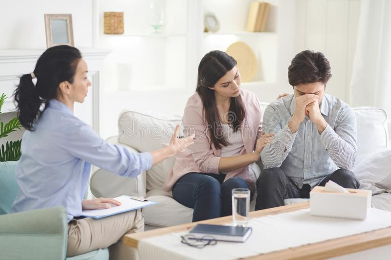 Loving wife supporting her husband during psychotherapy session. Young loving wife supporting her depressed husband during psychotherapy session with counselor royalty free stock photography