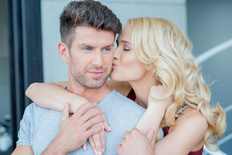 Loving woman kissing her husband or boyfriend stock photography