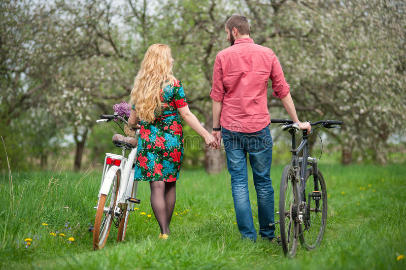 Loving young couple with bicycles. Beautiful young couple in love stand near the bicycles back to camera, holding hands and looking at each other in the spring royalty free stock photo