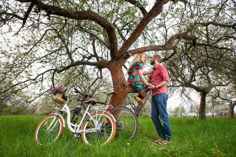 Loving young couple with bicycles in spring garden. Romantic lovers near the tree and bicycles in spring garden. Woman with long blond hair in flowered dress royalty free stock image