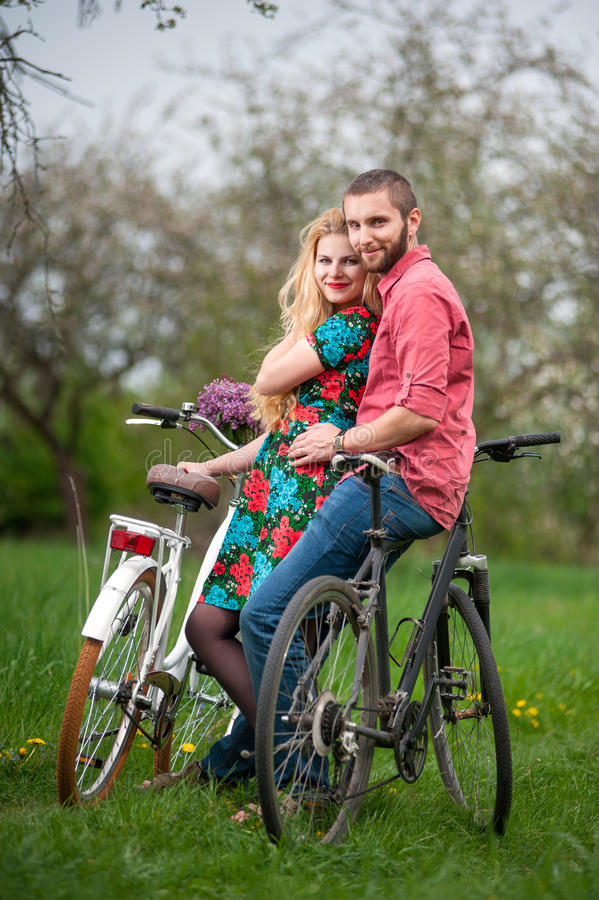 Loving young couple with bicycles. Two smiling lovers standing with bicycles and looking to the camera in the spring garden, against the background of trees and stock image