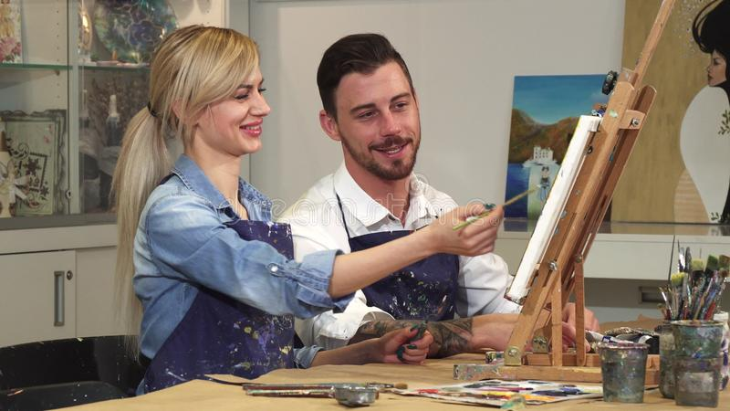 Loving young couple enjoying working on a painting at the Art Studio together stock photo
