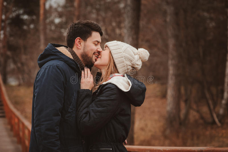 Loving young couple happy together outdoor on cozy warm walk in autumn forest stock photo