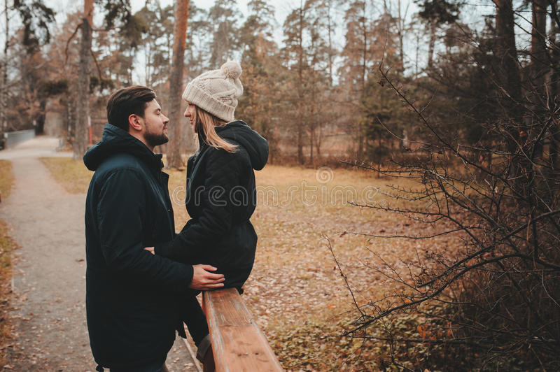 Loving young couple happy together outdoor on cozy warm walk in autumn forest stock photography