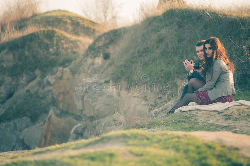 Loving young couple happy together outdoor, drinking tea. A guy with a girl on the lake at sunset drinks tea. stock image