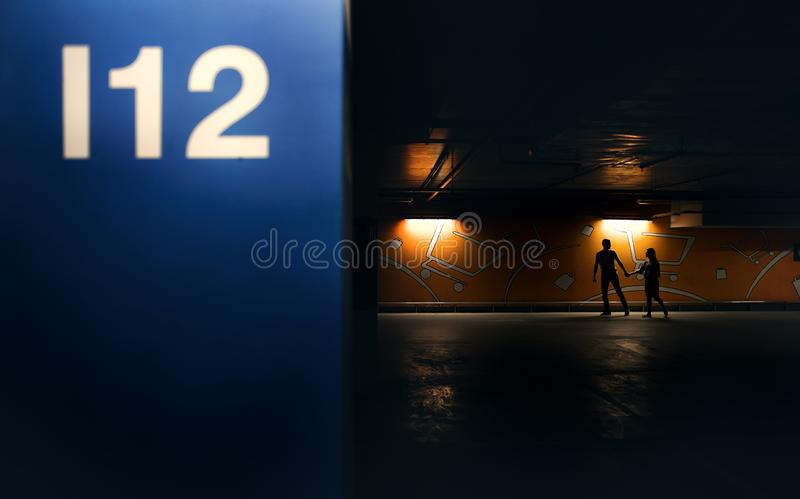 Young couple walking across the parking garage royalty free stock photos
