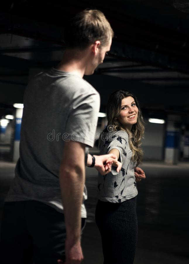 Young couple walking across the parking garage royalty free stock image
