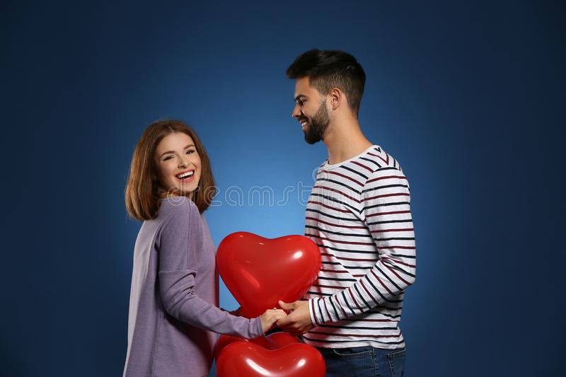 Loving young couple with heart-shaped balloons on color background. Celebration of Saint Valentine's Day royalty free stock images