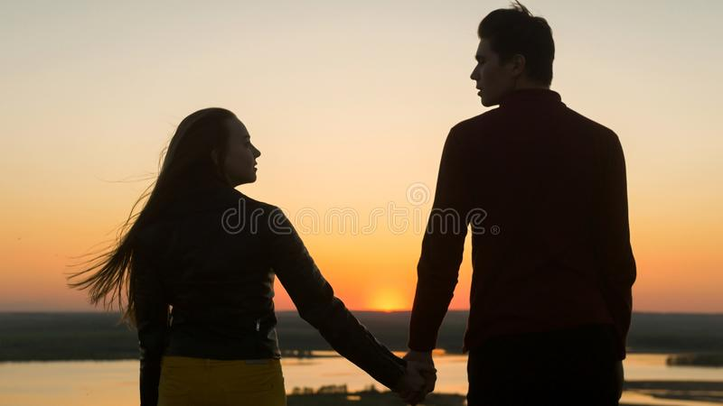 Loving young couple holding hands looking each other at amazing sunset outdoors stock photos