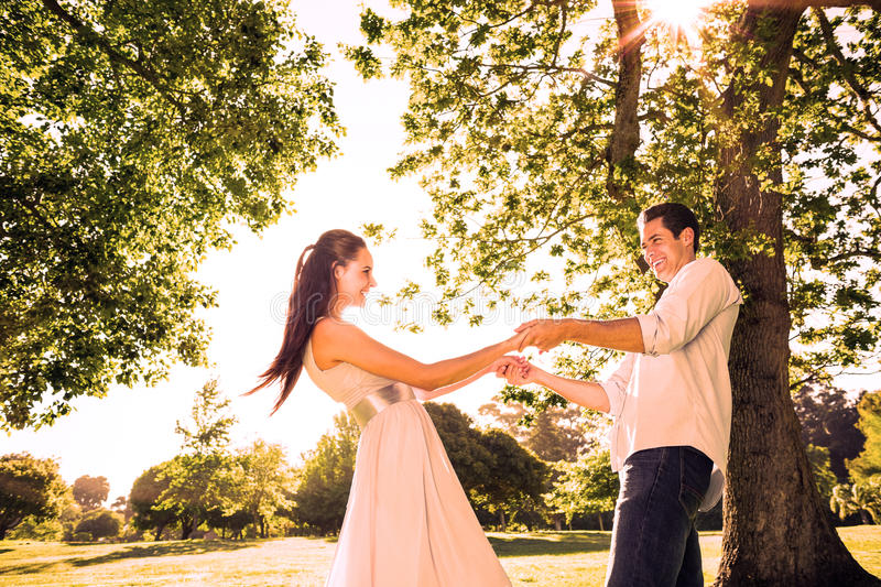 Loving young couple holding hands at park stock photo