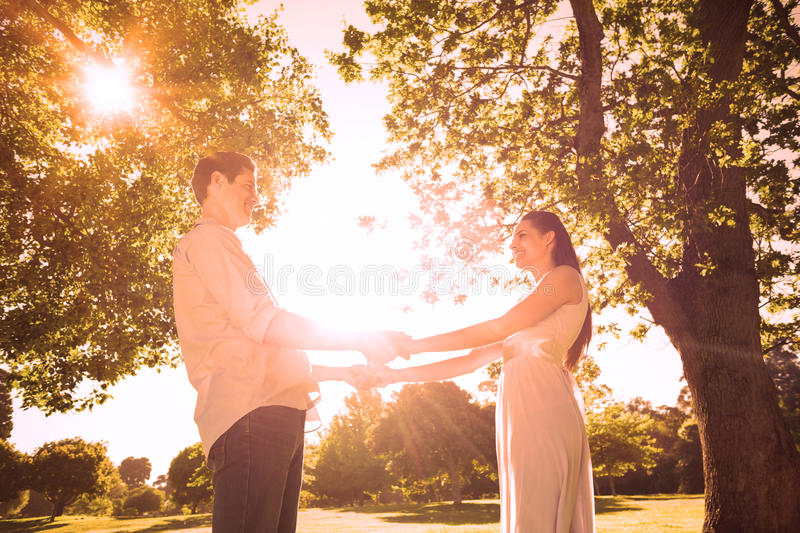Loving young couple holding hands at park royalty free stock image