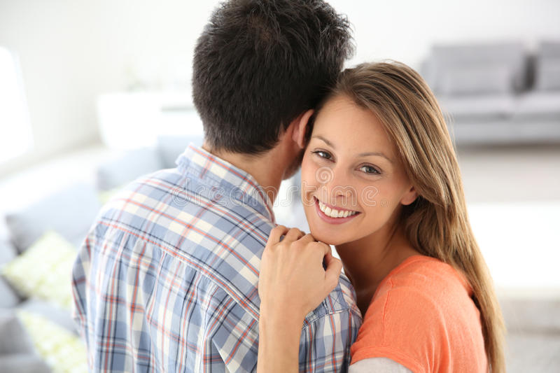 Loving young couple at home. Cheerful young loving couple at home stock photos