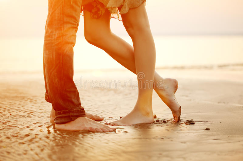 A loving young couple hugging and kissing on the beach at sunset royalty free stock images