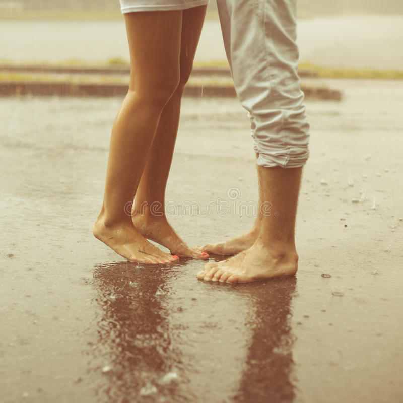 A loving young couple hugging and kissing under a rain. Lovers m. A loving young couple hugging and kissing under a rain. Two lovers, man and woman barefoot in royalty free stock image