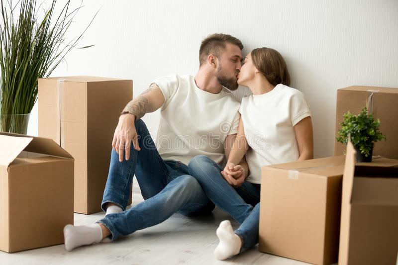 Loving young couple kissing, holding hands in new apartment royalty free stock photos