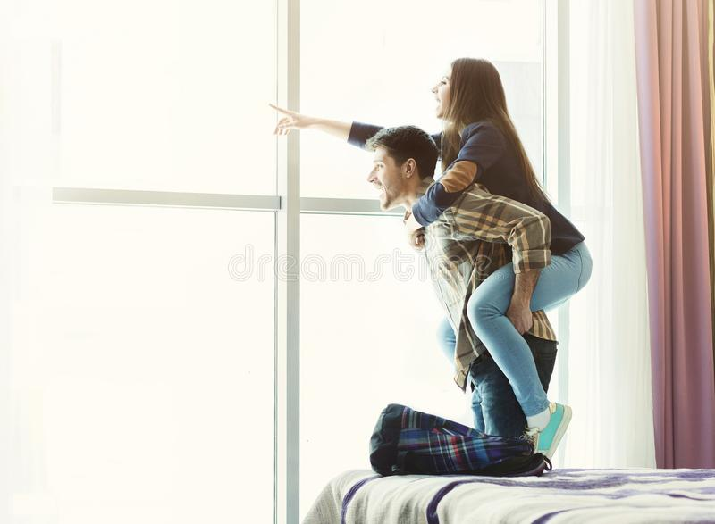 Loving young couple looking through window in hotel room royalty free stock photo